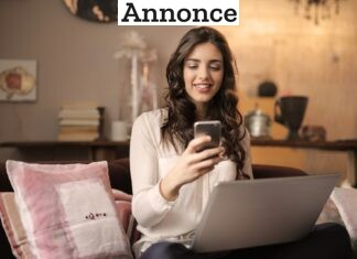 Kvinde sidder i sofaen med mobilen og computeren